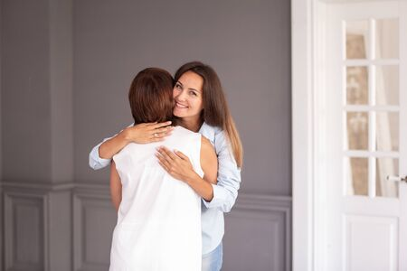 Adult woman hugs her elderly mother and they both smiling