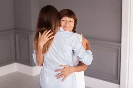 Elderly woman hugs tight her granddaughter and smile. Soft focus