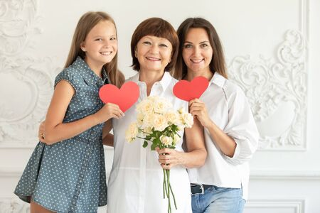 Mother, daughter and granddaughter hug and hold cardboard hearts and a bouquet of flowers
