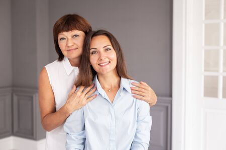 Charming adult woman sits on chair while her mother hugs her. Selective focus 写真素材