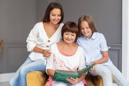 Daughter, mother and grandmother sit in chair with photo album in hands