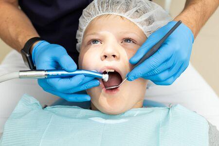 Le petit garçon est allongé sur une chaise de dentiste et s'est fait percer les dents par un stomatologue professionnel