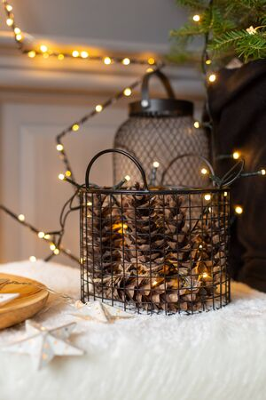 Closeup of basket full of fir cones on background of wall covered in shining garland. Selective focus