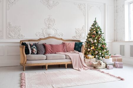 Christmas tree surrounded by giftboxes stands close to sofa in living room Banque d'images