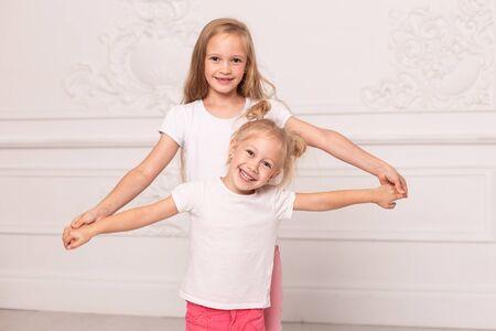 Zwei kleine blonde Schwestern, die im weißen Wohnzimmer miteinander spielen