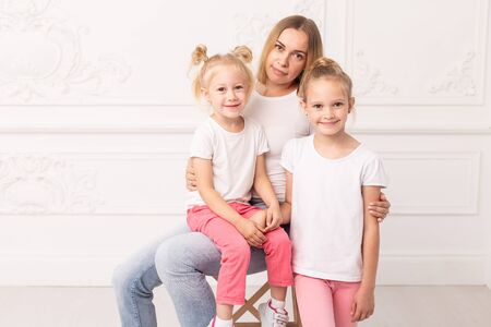 Mother who sits on chair and her daughters standing next to her pose for a photo
