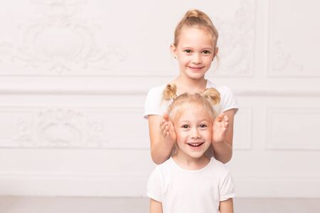 Older sister closes eyes of smiling younger one with palms