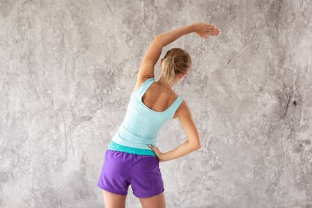 Blond sporty woman trunk bending as part of morning exercises back to the viewer
