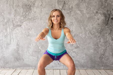 Cute young woman doing squating exercise and smiling