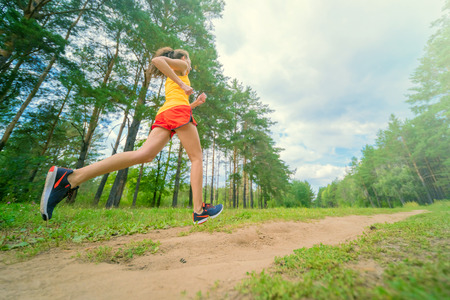 Running woman. Female runner jogging at the park. Girl training outdoors. Exercising on forest path. Healthy, fitness, wellness lifestyle. Sport, cardio, workout concept