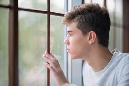 Ritratto di un bel giovane che guarda fuori dalla finestra. Adolescente di dolore 16-18 anni