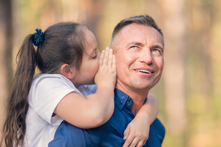 Little girl whispering in father ear, family trust concept