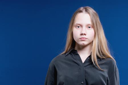 Retrato de una atractiva chica adolescente con largo cabello rubio sobre fondo azul.