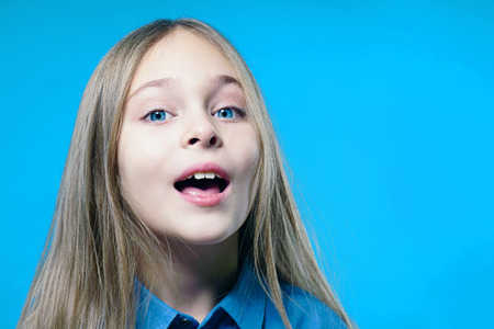 Portrait of a cute child girl with open mouth over blue background.