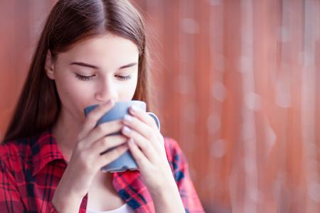 A closeup of a beautiful girl who is enjoying her tea. 免版税图像 - 116017447