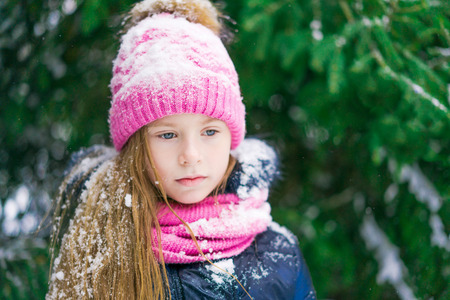 Beautiful little girl in pink hat looks thoughtful or sad in winter forest.