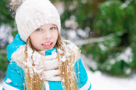 Cute blond kid with blue eyes in a winter forest smiling at camera. 免版税图像 - 116017451