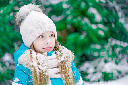 A girl child with snow on hair watching something in winter forest. 免版税图像