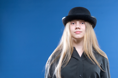 Blonde teen girl in a black hat over blue background 免版税图像