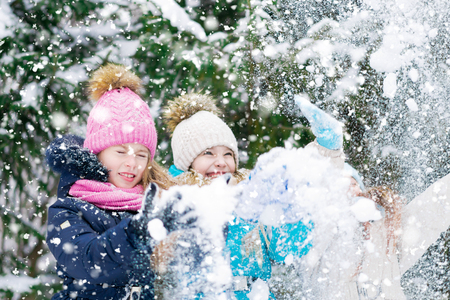 Little girls cheerfully playing by shaking snow from fir-trees in a winter forest. 免版税图像