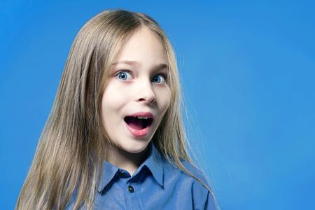 Überraschtes und erstauntes Kindermädchen mit offenem Mund, der die Kamera über blauem Hintergrund betrachtet.