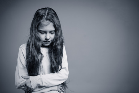 Stressed, depressed, unhappy child girl over gray background. 免版税图像