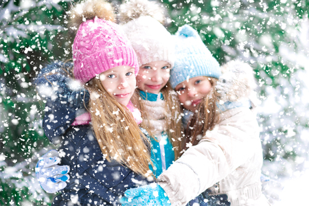 Beautiful little girl friends are hugging to take a portrait with the falling snowflakes in winter forest.