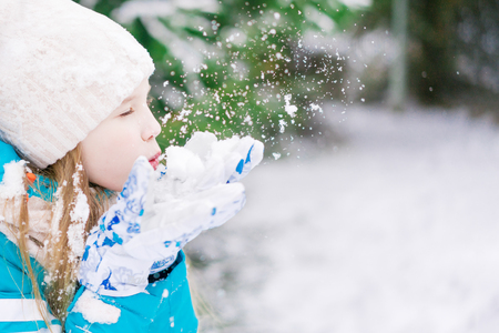 A profile of a cute girl child who blowing away the snow off her hands.