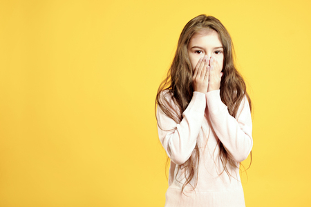 Sad little girl covers his face with hand over yellow background 免版税图像