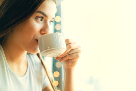 Girl is enjoying her cup of morning coffee with cheerful smile.