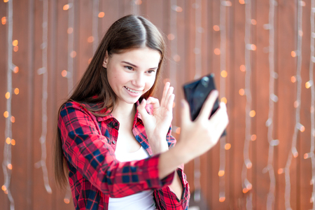 A cheerful teen girl is making selfie on cellphone.
