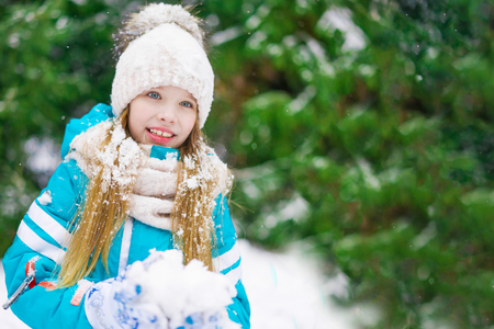A cute blond girl playing snowballs in winter forest.