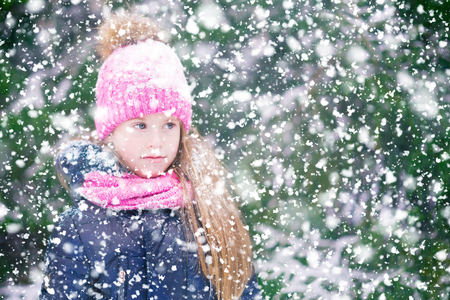 A pretty blond girl child wearing pink hat and scarf during a walk in snowfall looking thoughtfully.
