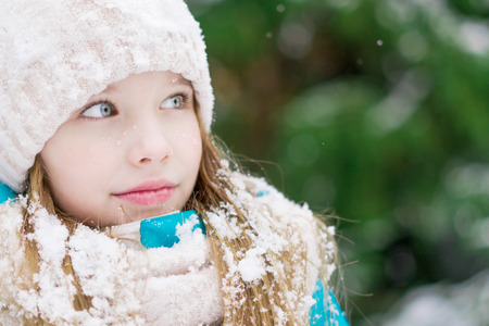 A girl child with blue eyes looking at something in winter forest.