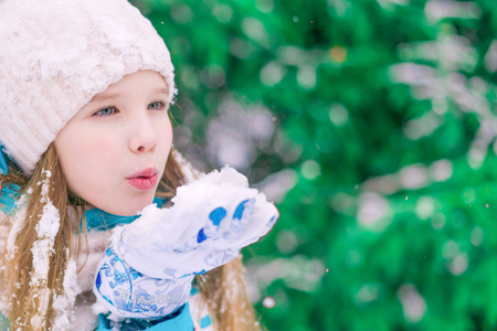 A closeup of a cute girl child who blowing away the snowflakes off hand.