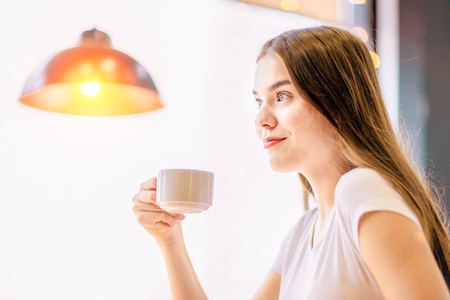 A girl is drinking coffee and thoughtfully smiling. 免版税图像