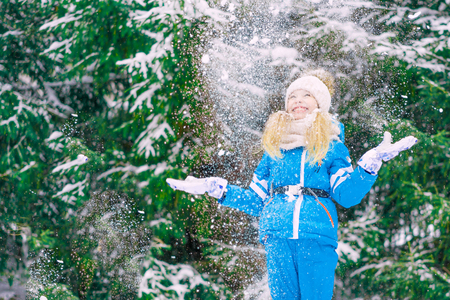 Happy blond girl throwing up snow over a fir-trees background.