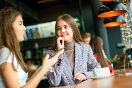 Two teenage girls smiling and gesticulating having friendly conversation.