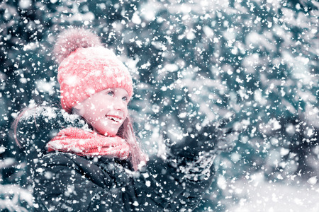A girl is smiling and catching snowflakes with her hands in a winter forest.