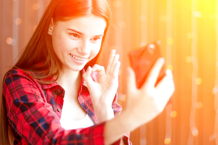 A teen girl is smiling to camera of her cell phone showing