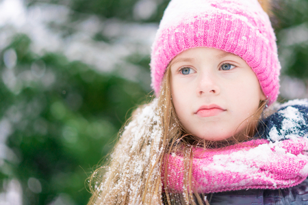 A cute little girl with blue eyes with a serious look outdoors.