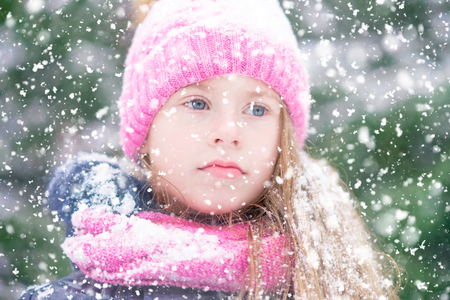 A blond girl kid with blue eyes is looking thoughtfully at falling snow.