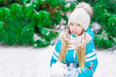 A beautiful blond child with a snowball in hand walking in a winter forest.