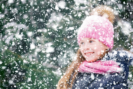 Beautiful girl child with a cute smile on a walk in forest during snowfall. 免版税图像