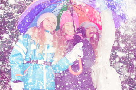 Happy little girls cheerfully laughing in snowy forest looking up and raising hand.