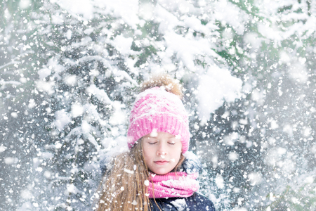 A head of a beautiful little girl in pink hat with closed eyes in a snowfall background. 免版税图像