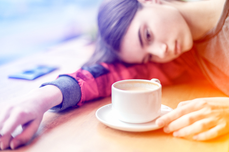 A girl looks depressed have laid her head down on coffee desk with a cup of coffee on it.