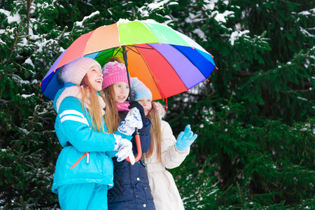 Three girl kids standing together in a winter forest under colorful umbrella.