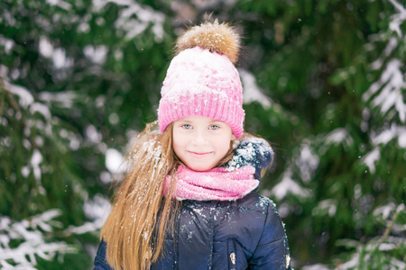 A portrait of a blond blue eyed girl child in pink hat and scarf among snowy fir-trees. 免版税图像