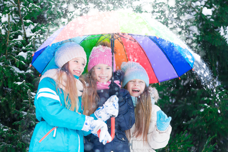 Three happy little girls hiding from snowfall under colorful umbrella in winter forest. 免版税图像